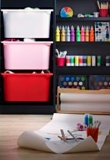 Dormitorio con pared de pizarra y almacenaje de IKEA con muchas pinturas de colores.