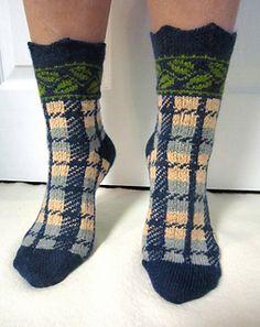 Ein Spitzenbündchen, kombiniert mit 2 sehr gegensätzlichen Mustern. Die Socke wird mit einer Grundfarbe und 2 oder 3 Kontrastfarben von oben nach unten gestrickt. Die Spickelabnahmen sind unter der Sohle plaziert.