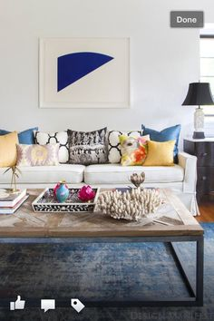 Beautiful lounge room colours. White lounge, blue rug, wall art, yellow, blue, black and white cushions pillows.