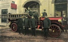 Eight uniformed Mansfield Firefighters surround MFD Auto truck number 1, which is parked in front of the City Hall/Main Fire Station on Park Avenue West at South Walnut in 1915. Two non-uniformed men stand near the engine of the truck, one holding a stoogie between his fingers. Visible to the left of the photo is the conveniently located bakery run by Henry Boebel at 11 Park Avenue West.