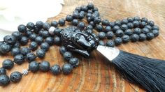 *This hand knotted mala necklace is made with 108 8mm lava stone beads. * At the half point there is an extra counter bead made of sterling silver. *Guru bead is a beautiful resin Buddha. *Beads are strung on super strong pearl cord. *Finally a tassel pendant completes the design. *Length: This necklace is 42 inches long in total and the tassel end hangs down a further 5 inches.  ***Lava stone also known as basalt literally comes from the core of the earth. It is formed when molten magma…