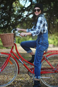 Nice contrast, denim overalls riding a red bike.