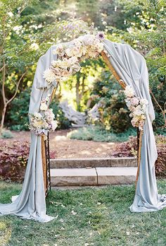 A romantic blue fabric altar with fluffy white roses, dahlias, and dusty miller | Brides.com