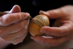 A woman, paints an traditional Lusatian Sorbian folk Easter egg in traditional Sorbian motifs with hot wax at the annual Easter egg market in Schleife, near Hoyerswerda, Germany.