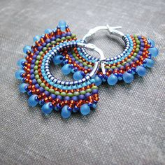 Frosted blue teardrops along the edge of these beaded hoops add an unusual touch of color to these bohemian hoops.    Using the brick stitch technique, I wove tiny seed beads around the perimeter of these sturdy sterling silver hoops, using nymo thread, a strong multifilament thread favored by bead artists. The beadwork on these earrings will not flop around as I use a firm tension in my weaving, but it is slightly flexible. Store your earrings flat when not wearing them, and I would…
