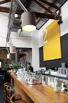 I chose this photo because of the mixture of styles. The yellow and black behind the cliounter is very modern, but exposed ceiling and light fixtures have more of an industrial feel to it making it very stylish and cozy.
