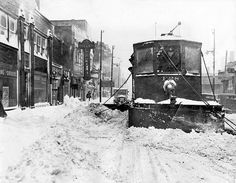 A streetcar equipped with a snowplow clears a Chicago street in 1939.