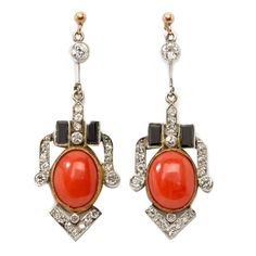 1920s Art Deco Coral Onyx Diamond Gold Platinum Dangle Earrings.  Europe, 1920s. Composed by 2 cabochon-cut coral. Decorated by 8 brilliant-cut diamonds, 34 round-shaped diamonds weighing ca. 1,16 ct. Accented by 4 rectangular shape onyx. Total weight: 5,96 g. Length: 1.5 in ( 3,8 cm ), Width: 0.59 in ( 1,5 cm )