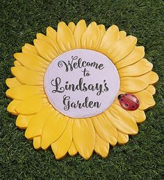 "Our Personalized Sunflower Garden Stone features vibrant yellow sunflower petals and a ladybug accent, it's a cheerful addition to your loved one's yard or garden. Best of all, you can personalize it with ""Mom"", ""Grandma"" or any name, creating a truly unique gift. Sunflower Garden, Yellow Sunflower, Summer Flowers To Plant, Planting Flowers, Lady Bug, Garden Plaques, Family Garden, 21st Gifts, Garden Stones"