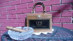 """""""JFR Premium Rolled Cigars"""" cigar box purse.  Purse has been re-hinged (when necessary) so that the purse will open at the top and artwork is displayed """"right-sides"""" up when carried. Finished with bamboo handles(s), tassel, sealed and lined with fabric."""
