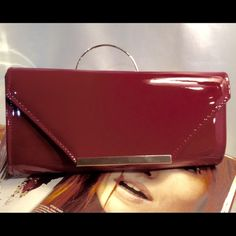 Gorgeous Magenta Clutch This trendy patent leather clutch features gold tone hardware, gold detachable shoulder strap, satin lined with one slip pocket, snap closure. Measures: 11W X 5H X 2D (This closet does not trade or use PayPal) Bags Clutches & Wristlets