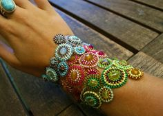 Summer Bubbles Bracelet -- $44  from Mariquez on etsy.com (Netherlands)  Icy blue and lilac (top)  Pink and gold tones (middle)  Green and gold tones (bottom)  Beaded circles with a glass bead center are attached to each other as a bracelet. It has a beaded toggle clasp with 2 eyes, bracelet is NOT elastic.