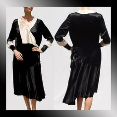 Silk dress dating to the 1920s. The dress is black with a white collar that extends on the right side over to the left side of the waist. Th...