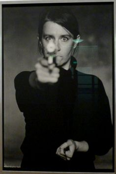 In the photograph Self-Portrait (1993/2011), Cecilia Edefalk is holding a revolver in one hand, aiming it at me as a viewer. Her other hand is holding a camera trigger. However, the moment the picture was taken the revolver was pointing at a camera. As she aims at the camera lens she takes a self-portrait.