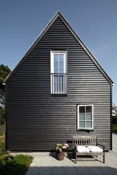 A simple wood framed house painted black (window frames included) in New England. Photo via Katy Elliott.