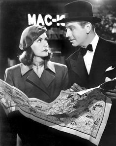 """Greta Garbo and Melvyn Douglas reading map inNinotchka (1939). """"Garbo laughs.""""Ninotchka is Garbo's first full comedy, and her penultimate film. It is one of the first American movies which, under the cover of a satirical, light romance, depicted the Soviet Union under Joseph Stalin as being rigid and gray when compared to the free and sunny Parisian society of prewar years."""