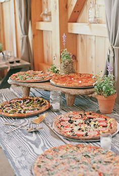 Brides.com: . A rustic pizza station with pies served on a picnic table decorated with mason jar candles and potted plants.