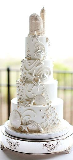 Beach themed wedding cake covered in white shells and decor.
