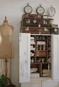 so much to love here - suitcases, clocks, cabinet, dress form <3