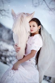 White horse with soft pretty face and girl hugging his head in her hand. Snowy…