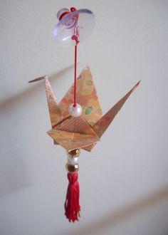 - Um lindo tsuru com estampa em tons marrons e amarelos com pequenas avelãs. <br>- Feito com papel japonês estampado no tamanho 15cm x 15 cm. <br>- Tem pequenos cristais em tons combinando e pérolas, além de uma franja. <br>- Este modelo vem com ventosa.