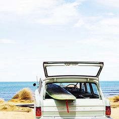 Surfboard in the back of a Holden on the beach. From Kara Rosenlund's travels.