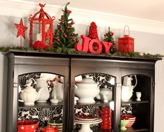 lights and greenery above the kitchen cabinets  wreaths hanging