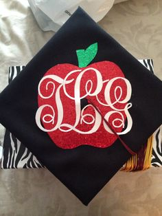 I like the apple but not the craziness of the font for the letters… They would be too hard to see far away Teacher graduation . Teacher Graduation Cap, Graduation 2016, Graduation Cap Designs, Graduation Cap Decoration, Grad Cap, Graduation Letters, Graduation Ideas, Grad Pics, Graduation Pictures