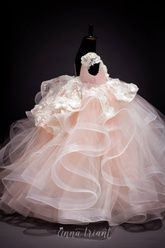 Lusciously gorgeous gown in a gentle color scheme of cream and blush, layered tulle and horsehair braid skirt, additional underskirt, delicious high-low peplum with 3d blooms, fitted bodice with lace cap sleeve, pearl accents and 3d crystal and satin flowers.