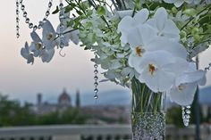Tall centerpiece detail with hanging crystals and white phalenopsis