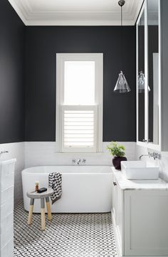 mid sized trendy bathroom gray paint, white cabinets, a freestanding tub black and white tile