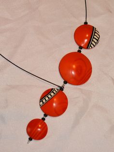 Hollow polymer clay beads strung onto an assymetrical necklace.