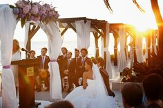 Invitados a una boda bajo una pérgola frente al mar