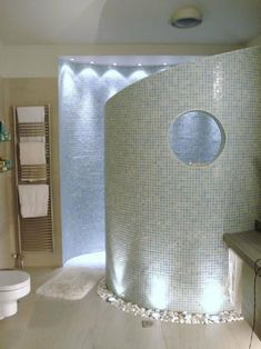 Curved walk in shower with river rocks