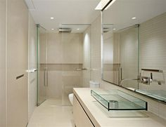 Awesome modern minimalist small bathroom with white toilet and huge mirror and glass vessel sink vanity also cream ceramic tile and glass door and square rainfall shower head also ceiling lights.