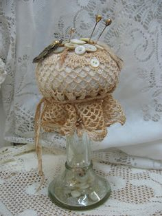 Pin cushion made on vintage candle holder with a doily and pearl buttons