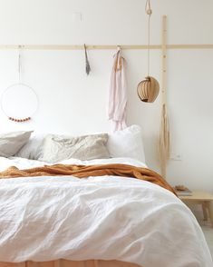 """The master bedroom has a hanging peg rail, both horizontal and vertical, that Ilona put together herself: """"Easy job; it's just simple wood."""""""