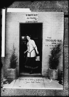 The Village Art Gallery, Yours as a Taking Proposition. c. 1910s - 1920s. Portrait of Jessie Tarbox Beals standing in the doorway of the Village Art Gallery.