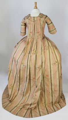 Rear view, robe à la francaise, France 1775-1799. Ivory and pink striped silk brocade with polychrome floral sprays, decorated with self fabric padded diamond bands, serpentine ovals and self fabric silk brocade bows edged in lace, linen lining.