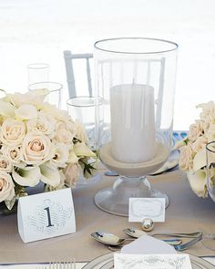 For this seaside tablescape, arrangements of white roses and calla lilies are set off by candles nestled into sand-filled glass vessels.