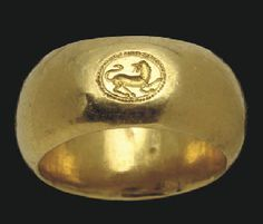 AN ETRUSCAN GOLD FINGER RING CIRCA LATE 6TH-EARLY 5TH CENTURY B.C. The hollow broad hoop flat on the interior, rounded on the exterior, engraved with a lion in profile to the right, its head turned back, the tongue lolling, the tail upraised, enclosed within a hatched border  15/16 in. (2.4 cm.) wide; ring size 7½