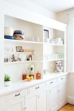 White kitchen with built-in shelving.