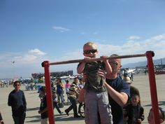 Military man helping child do a pull up.