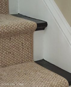 Tone on Tone: I chose a wool sisal style staircase runner with very narrow binding. It's installed about 3 inches from the sides (and cut out around the newel post) in the Hollywood style, which is tailored and bespoke. The big area rug is the same, but with a different binding. Larger area rugs do wonders for small spaces!