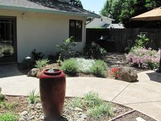 AFTER: Wow!  What a difference a design can make with complimentary plantings, curved paths, outdoor lighting, and a bright red wonderful fountain!
