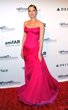 Uma Thurman looks ravishing in a sweeping, fuchsia Atelier Versace gown at the amfAR Inspiration Gala in New York City.