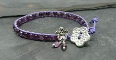 Purple leather and glass bead bracelet with flower button and flower charm £10.00