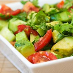A fresh summer side dish: tomato, avocado, cucumber salad with cilantro in lime olive oil dressing.