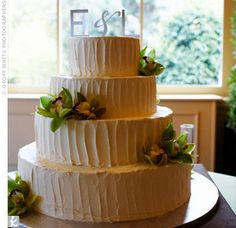 Cymbidium orchids and a brushed-metal monogram topper finished off the four-tiered buttercream cake.