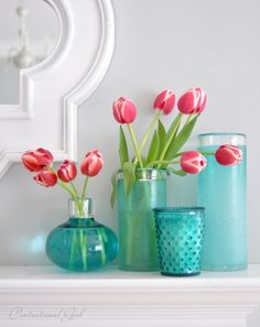 coral tulips blue vases on mantel
